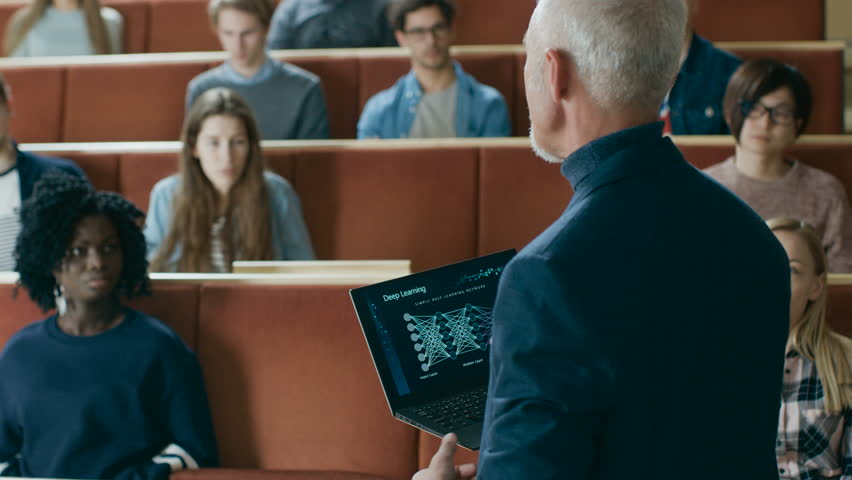 Back View of the Professor Giving Lecture on Computer Science to a Classroom Full of Multi Ethnic Students. Teacher Holds Laptop with Deep Learning, Artificial Intelligence Infographics on the Screen.