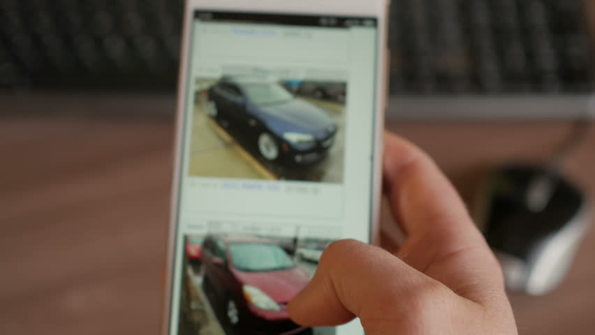 A man chooses to buy a car on the site. Looking at used vehicle to buy on a smartphone app. Close Up. Screen is blurred. 4K UHD.