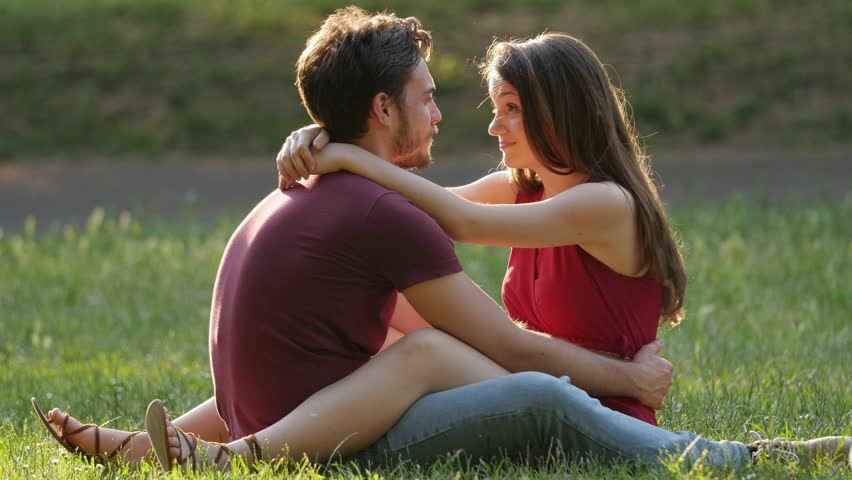 Happy young Couple Laughing And talking While Sitting In The Park On The Lawn   Shutterstock HD Video #1009955084