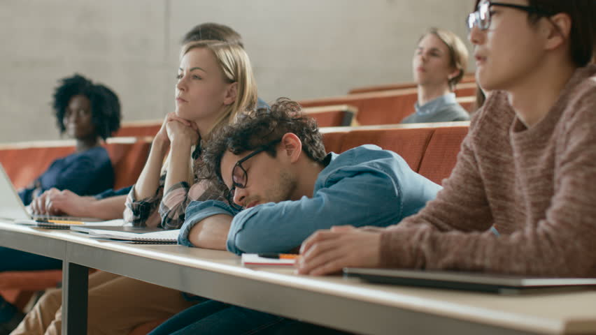 Tired Male Student Sleeps on a Lecture at the University. Exhausted and Overworked Young Male.  Shot on RED EPIC-W 8K Helium Cinema Camera.