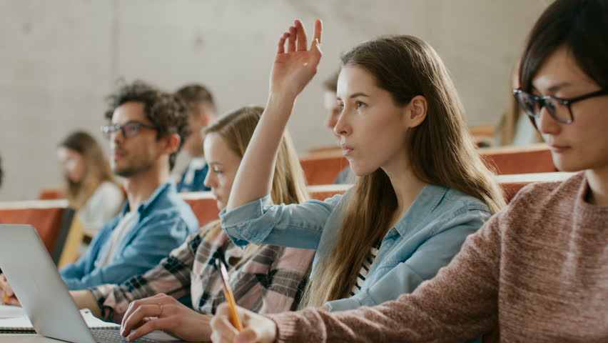 Beautiful Young Student Uses Laptop while Listening to a Lecture at the University, She Raises Hand and Asks Lecturer a Question. Multi Ethnic Group of Modern Bright Students.