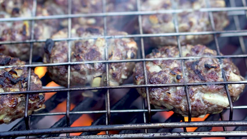 Shallow depth of field closeup of cooking kofta in grilling basket on hot grill.   Shutterstock HD Video #1009993439