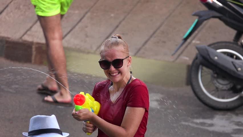 Young Female Caucasian Tourist Shooting Water Gun at Songkran Festival (Thai New Year)