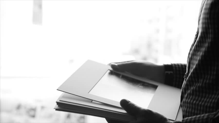 Man passing photos to woman. Close-up of young male hands passing the photosthe female hands, monochrome image. Slow motion, sketch, isolated.