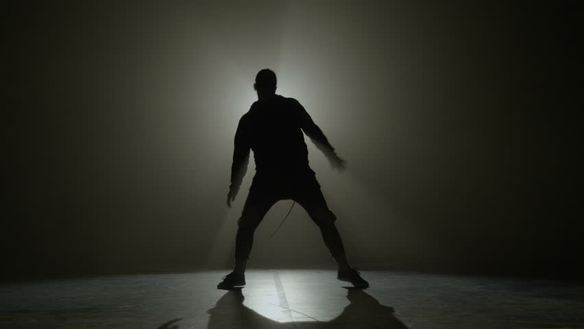 Silhouette of a talented young dancer dancing hip hop street dance on a stage in front of the spotlight