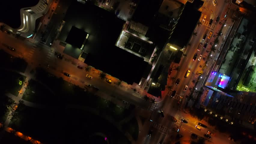 Aerial over city facing down tilt up reveal night