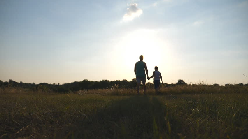 Silhouette of father and son walking on the field at sunset and holding hands of each other. Happy family spending time together outdoor. Active lifestyle. Slow motion Rear back view #1010040143