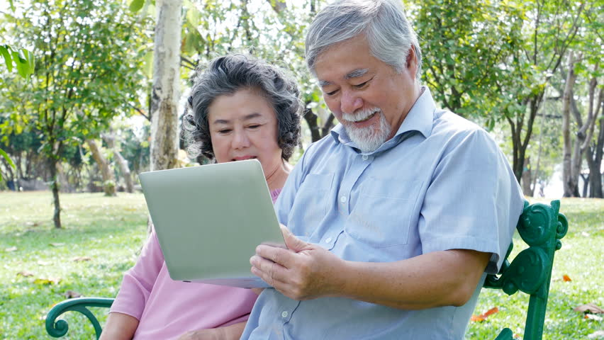 Asian couple elder people relax at park together. Elder people using laptop with happy emotion. People lifestyle concept    Shutterstock HD Video #1010045951