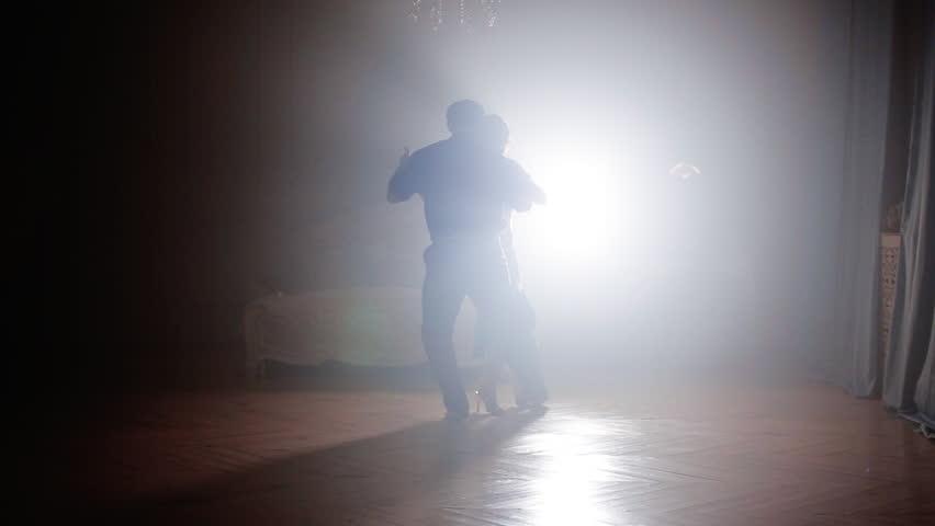 Couple dancing latin dance in the fog