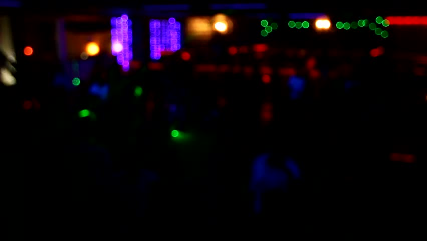 People dance have fun and relax in the nightclub blurred background. Flashes of light, beautiful blurred lights on the dance floor, a lot of people relax at night in the club. No focus video  #1010055887