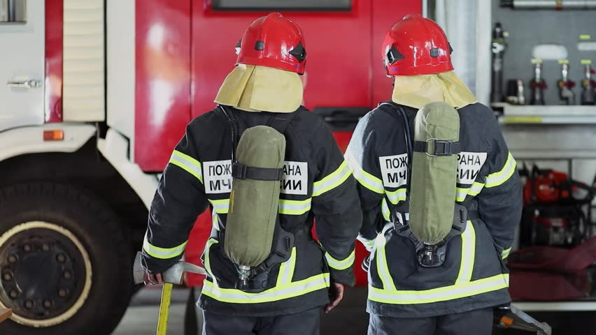 Two firefighters turn around in protective coats with oxygen cylinders near fire truck