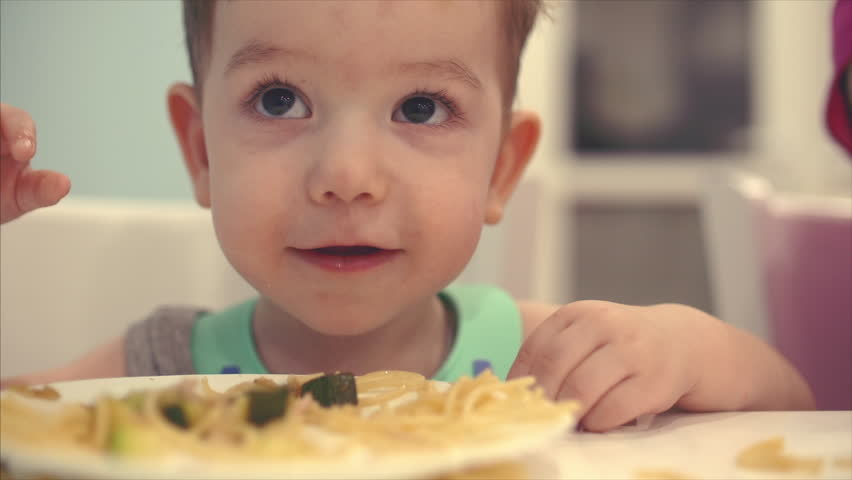 Small child is sitting at a table in a bib and eat his own spaghetti, the baby eats willingly. | Shutterstock HD Video #1010063417