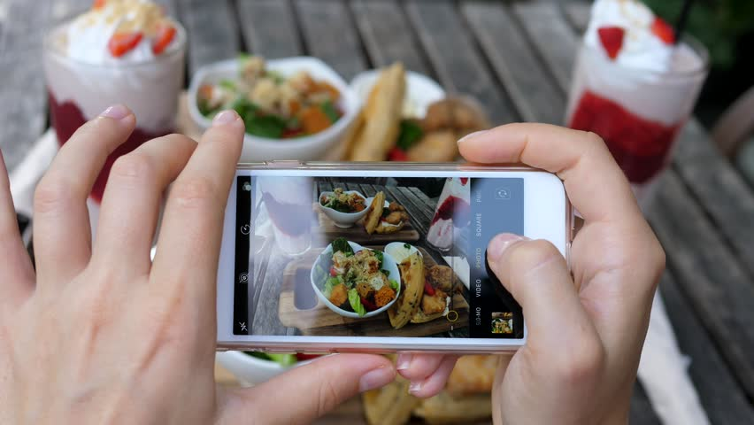 Hands Holding Phone Taking Photo Of Food In Restaurant #1010064257