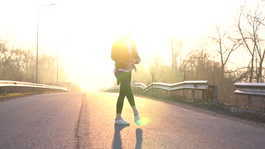 A ballerina woman dances at dawn in the middle of the road arabesque ballet, slow motion | Shutterstock HD Video #1010066786