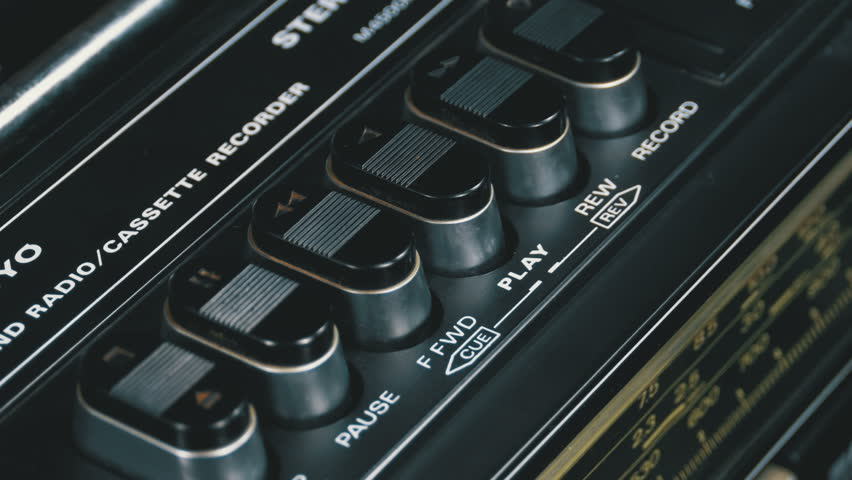 Pushing Button on a Tape Recorder, Play, Stop, Rec, ff, Rew. Close-up. Man finger presses playback control buttons on vintage audio cassette player. | Shutterstock HD Video #1010096483