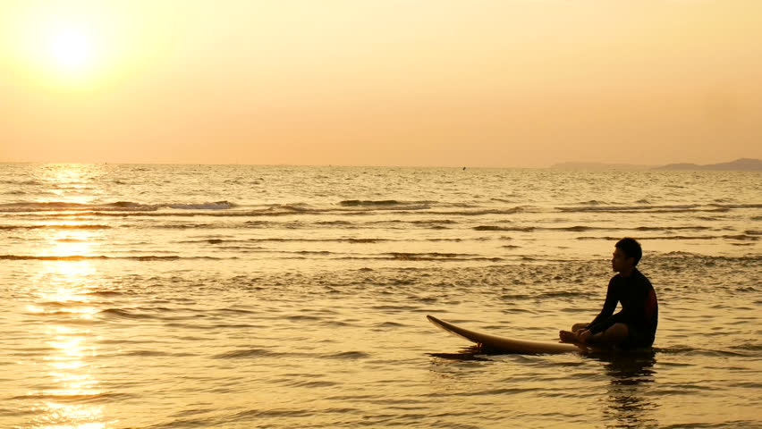 4K. silhouette of surfer man relax by sitting on surfboard over the sea at sunset on tropical beach. sport and recreation for summer season concept Royalty-Free Stock Footage #1010107094