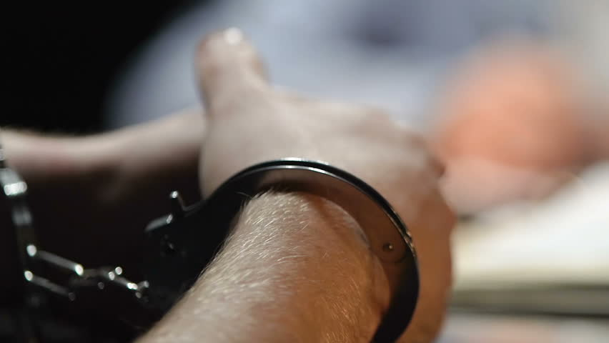 Detained thief answering lawyer questions in police station, handcuffs close up #1010108132