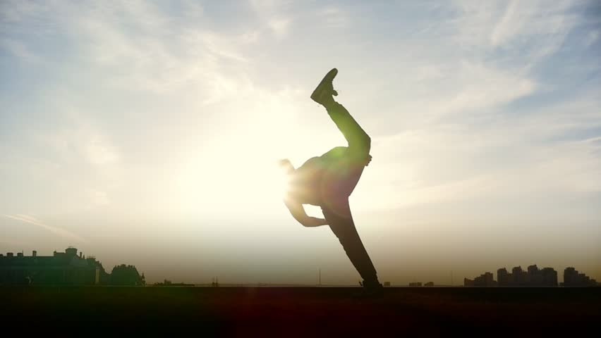 Slow-motion - young male Parkour tricker jumper performs amazing flips in front of the sun   Shutterstock HD Video #1010113082