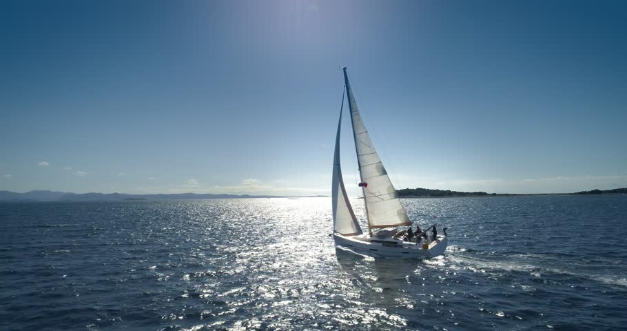 Yacht sailing on opened sea.  Yachting with sails up at windy day.