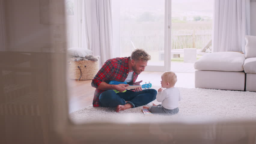 Dad sits playing ukulele with toddler, seen through window
