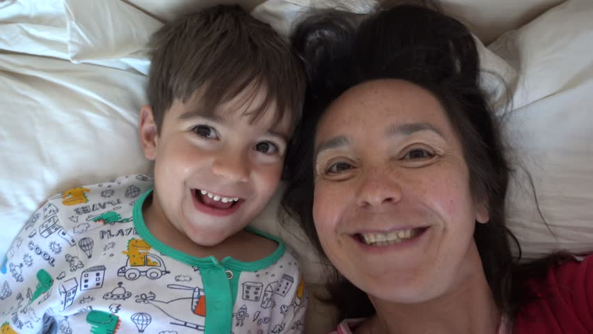 4K Selfie funny mother with son speaks on camera in the morning in the bed