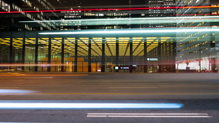 Cars travelling down Bay street in downtown Toronto, Ontario Canada. Long exposure light trails show a fast paced city at night. Futuristic and modern architecture in the background. Royalty-Free Stock Footage #1010173457