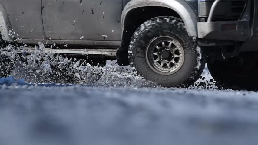 Drift on a big black car on a winter road outside the city and snow flies from under the wheels during a close-up turn | Shutterstock HD Video #1010180006