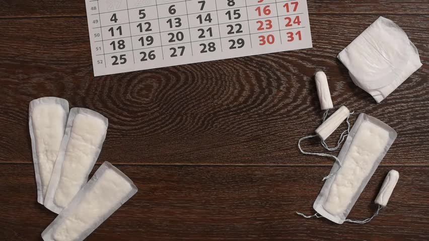 The girl marks the days of menstruation on the calendar and hygienic tampons and gaskets lie nearby | Shutterstock HD Video #1010180048