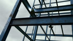 Worker soldering steel beam structure on new building