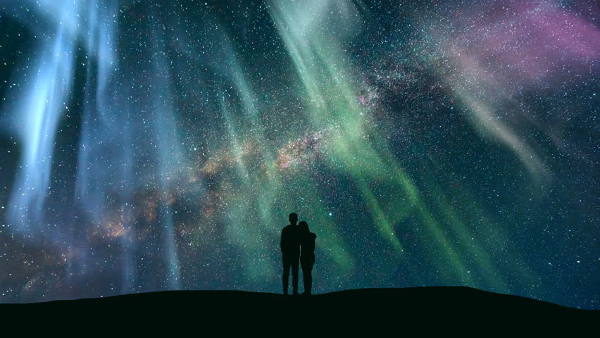 The couple standing against the northern light with a northern light. time lapse