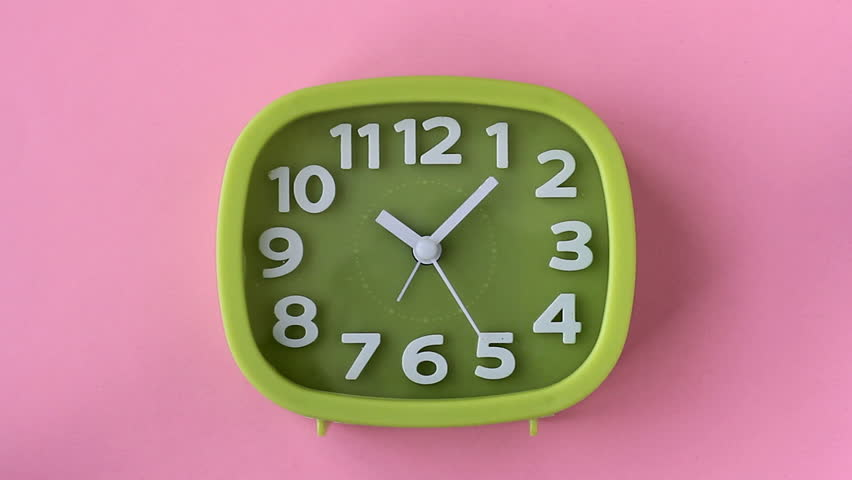Green clock with white numbers and arrows on pink background, Time Lapse | Shutterstock HD Video #1010211389