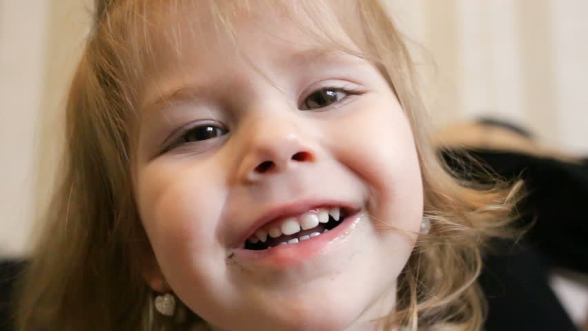 Funny baby smiling at the camera. The little girl has a grimy mouth. Close-up, bottom-up view, real-time, indoor, interior