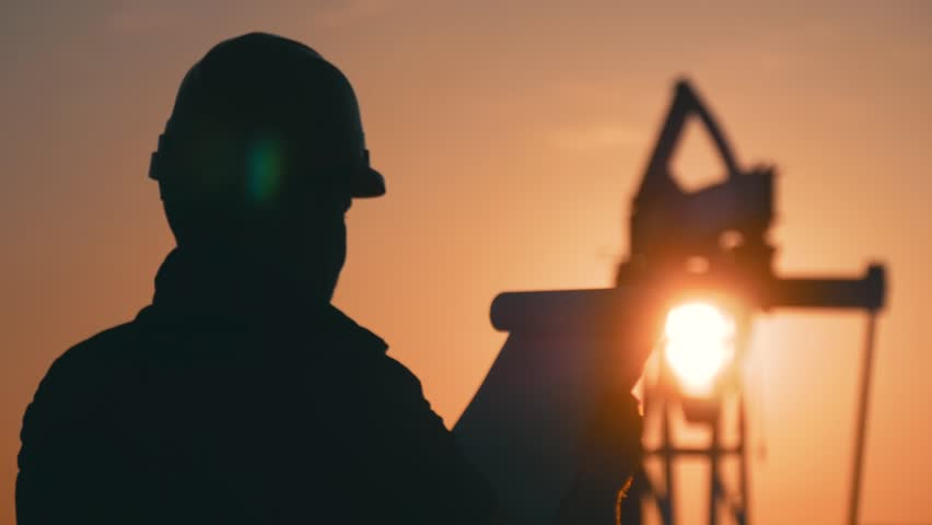 Silhouette of man engineer with clipboard and securities for the oil pumping unit overseeing the site of crude oil production at sunset.
