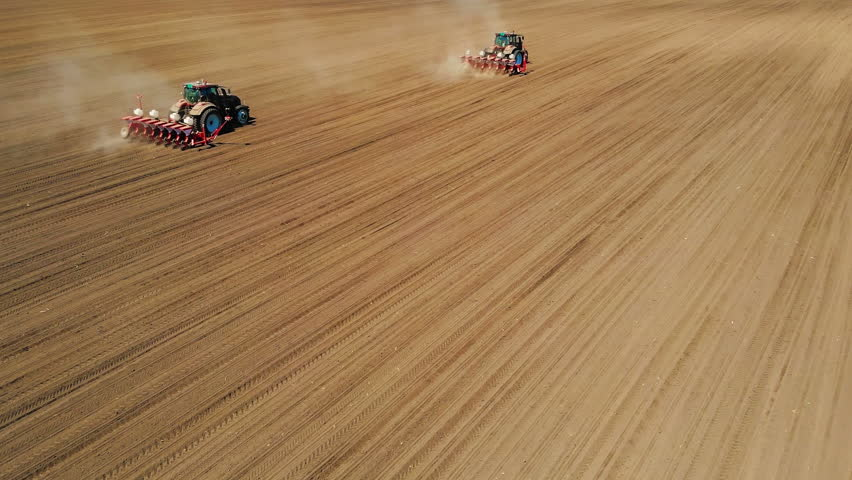 Aerial drone shot of a farmers in two tractor seeding, sowing agricultural crops at field | Shutterstock HD Video #1010219948