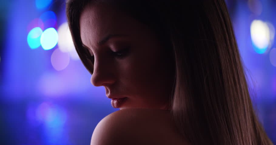 Dramatic side view close-up of beautiful woman on vibrant blurred background. Millennial woman in her 20s bathed in shadow looking dramatic with bokeh lights in background. 4k | Shutterstock HD Video #1010220455