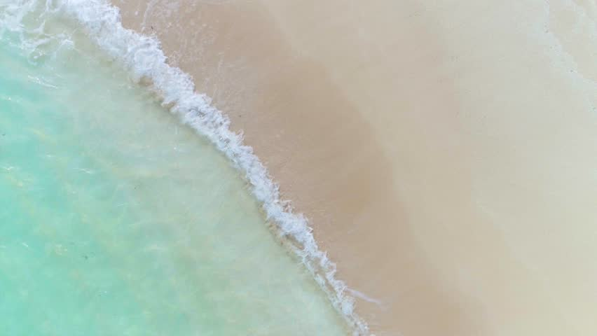 Bird's eye view of waves and sand over a Caribbean cay with turquoise waters #1010224547