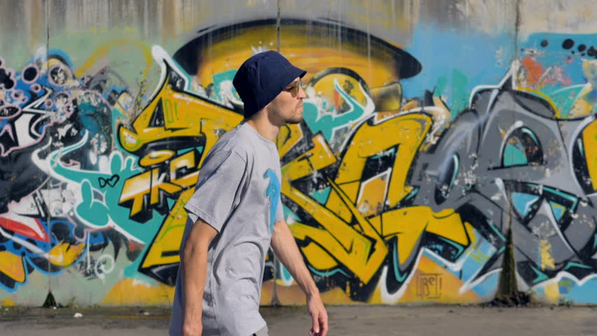 Young man is walking along the street with graffiti painting on the background and a spray in his hands