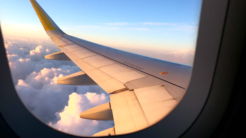Airplane flight. Wing of an airplane flying above the clouds with sunset sky. View from the window of the plane. Airplane, Aircraft. Traveling by air. 4K UHD video | Shutterstock HD Video #1010280311