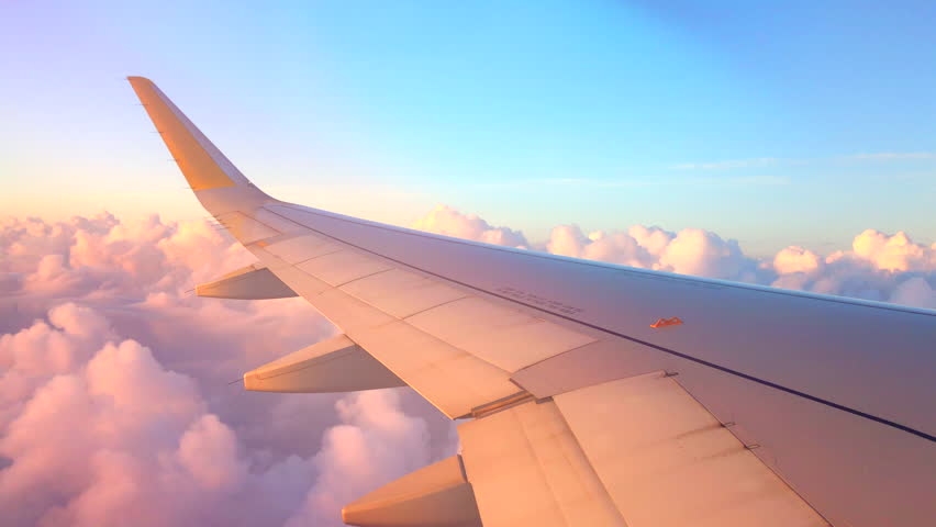 Airplane flight. Wing of an airplane flying above the clouds with sunset sky. View from the window of the plane. Aircraft. Traveling by air. 4K UHD video #1010280539