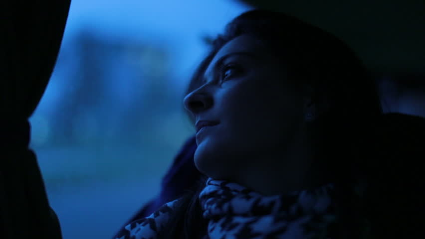 Woman pressing lips while traveling by bus in twilight hours of the night