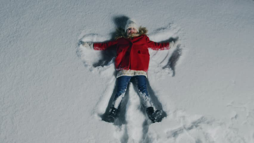 Top Down Footage of the Happy Cute Little Girl Falling into Snow, Lying and Making Snow Angel. Child Enjoying Winter Weather. Shot on RED EPIC-W 8K Helium Cinema Camera.