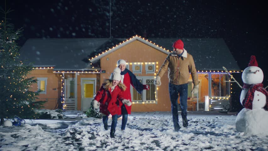 Lovely Young Family Running out of Their Idyllic House, Everything is Decorated with Lights and Garlands for Christmas Eve. Father, Mother and Cute Little Daughter Have Fun. Shot on RED EPIC-W 8K. #1010291762