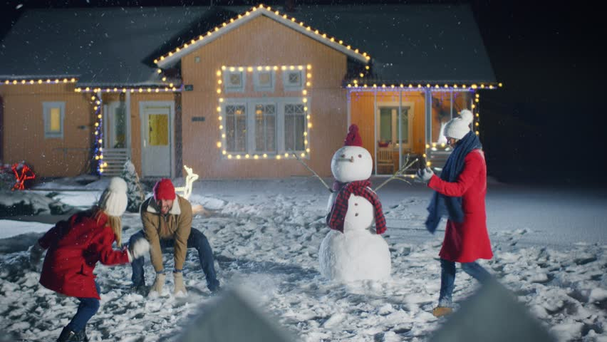 Happy Young Father, Mother and Cute Little Daughter Play in Snowballs, Running around the Snowman They've Build in the Backyard of Their Idyllic House Decorated with Garlands.  Shot on RED EPIC-W 8K. #1010291801