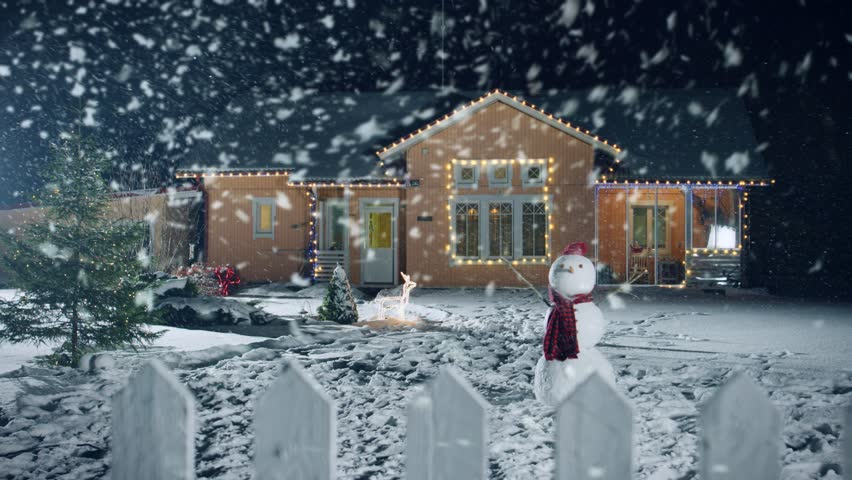 Footage of the Idyllic House Decorated with Garlands on Christmas Eve, Snowman and Christmas Tree stand on the Front Yard. Beautiful Winter Evening with Falling Soft Snow. Shot on RED EPIC-W 8K. #1010291837