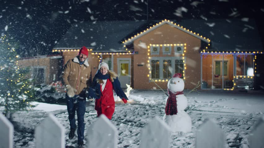 Young Beautiful Couple Holding Hands Running out of their Idyllic House, Everything is Decorated with Lights and Garlands for Christmas Eve. Man and Woman in Love.  Shot on RED EPIC-W 8K Helium Cinema #1010291840