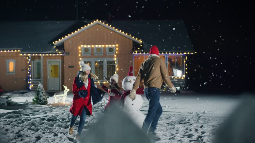 Happy Young Father, Mother and Cute Little Daughter Dance Mary Go Round around the Snowman They've Build in the Backyard of Their Idyllic House Decorated with Garlands. Shot on RED EPIC-W 8K Camera. #1010291876