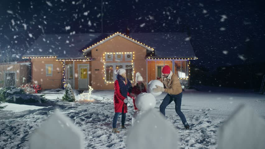 Happy Young Family Making Snowman in the Backyard of their Idyllic House. Father Rolls Snowball, Daughter and Wife Help Him. Family Spending Time Together one Winter Evening. Shot on RED EPIC-W 8K. #1010291891