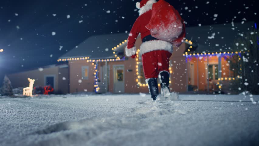 Santa Claus Carrying Red Bag over the Shoulder, Walks into Front Yard of the Idyllic House Decorated with Lights and Garlands. Santa Bringing Gifts and Presents. Shot on RED EPIC-W 8K Camera. #1010291906