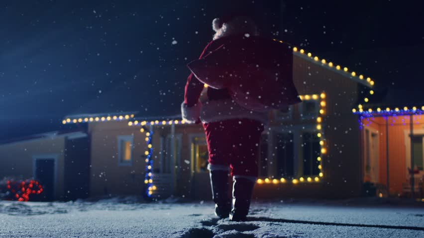 Low Angle Footage of Santa Claus with Red Bag, Walks into Front Yard of the Idyllic House Decorated with Lights and Garlands. Santa Bringing Gifts and Presents at Night.  Shot on RED EPIC-W 8K.