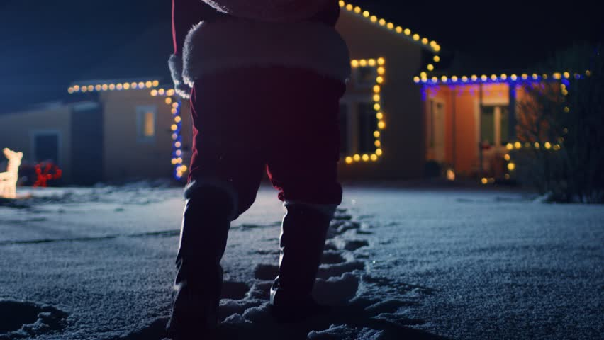 Low Angle Footage of Santa Claus with Red Bag, Walks into Front Yard of the Idyllic House Decorated with Lights and Garlands. Santa Bringing Gifts and Presents at Night. Shot on RED EPIC-W 8K Camera.